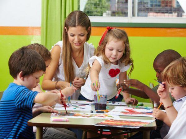 Воспитатель рисует с детьми в детком саду