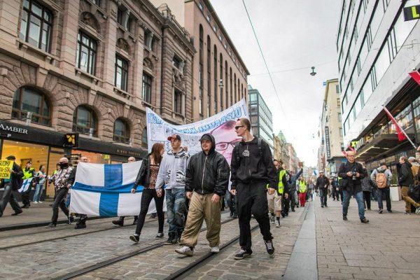 Демонстранты с флагами и плакатами идут по улице