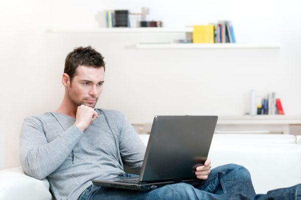 Молодой человек ищет работу через интернет