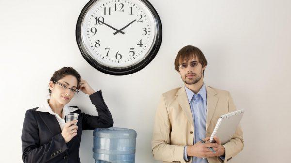 Работники офиса и настенные часы