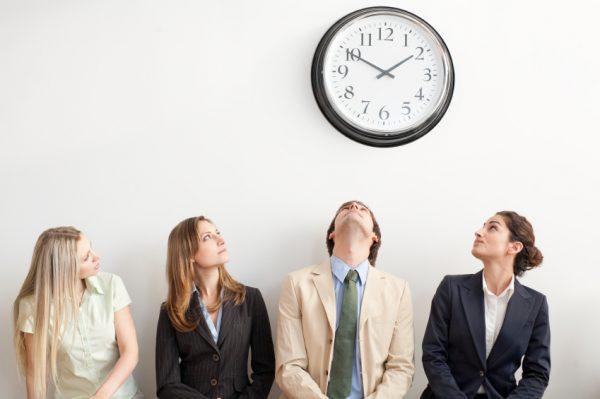 Молодые люди смотрят на настенные часы