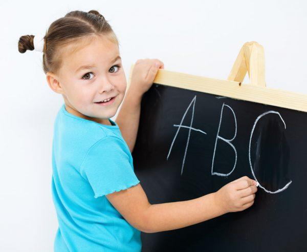 Девочка пишет на доске английские буквы