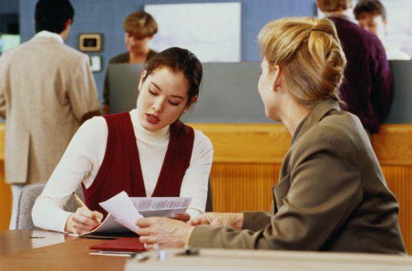 Девушка заполняет бумаги за столом