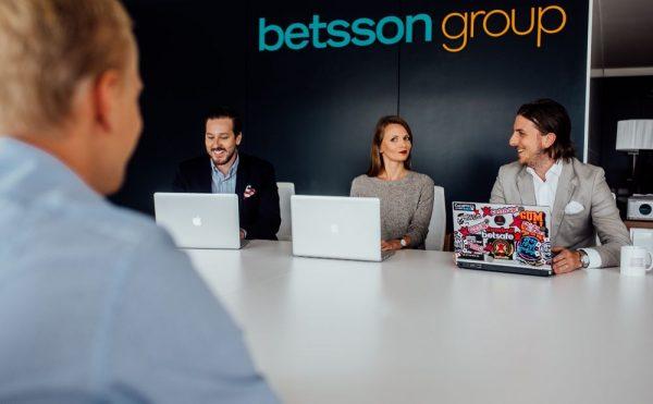 Люди за ноутбуками под логотипом Betsson Group