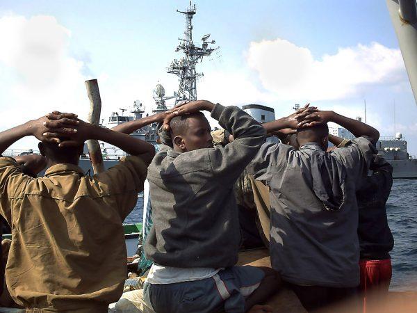 Пленные на фоне военного корабля