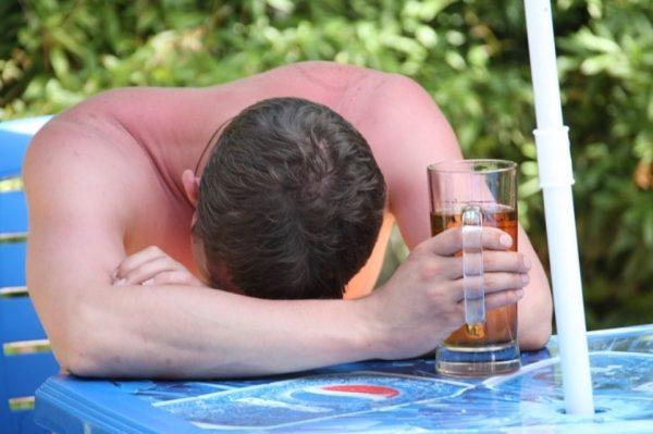Мужчина спит с бокалом пива за столиком