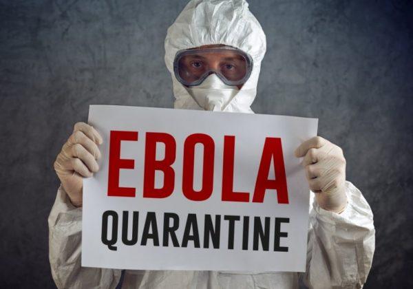 Человек в костюме биозащиты с плакатом