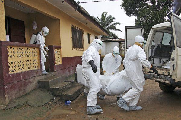 Медики в костюмах биозащиты выносят из дома труп