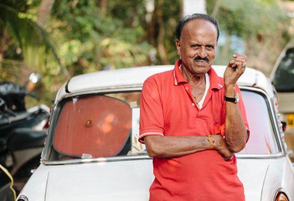 Индус на фоне старенького автомобиля