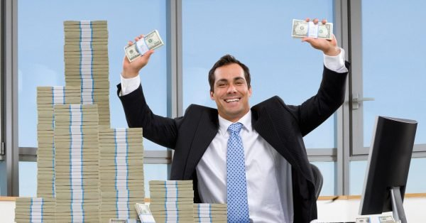 Мужчина с пачками долларов на фоне окна