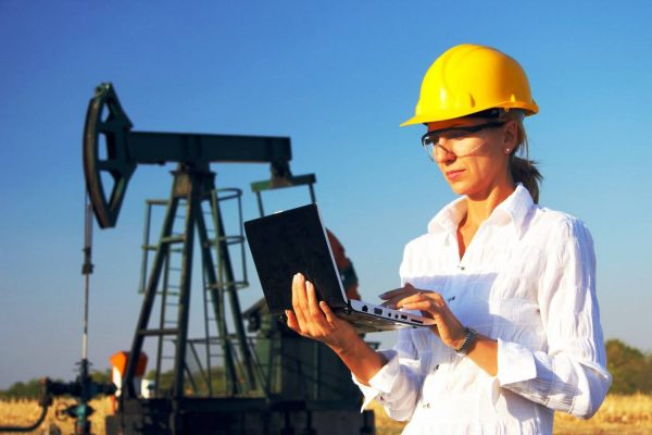 Женщина в каске на фоне нефтяной вышки