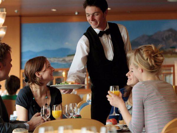 Официант подаёт блюдо клиентам