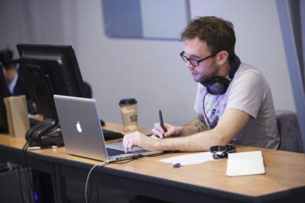 Мужчина с ручкой за ноутбуком