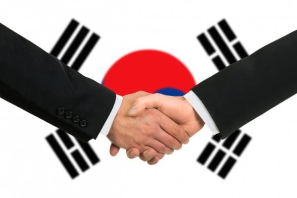 Рукопожатие на фоне корейского флага