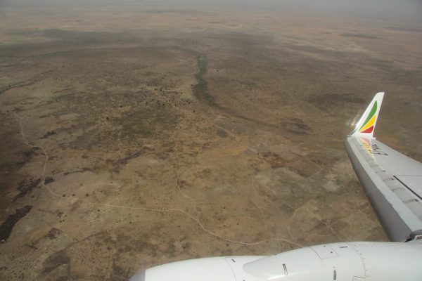 Крыло самолёта над африканской каменистой пустыней
