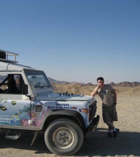 Водитель возле джипа на фоне пустыни