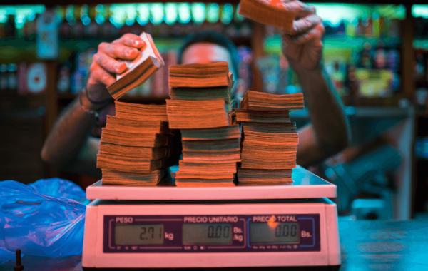 Человек кладет пачки денег на весы