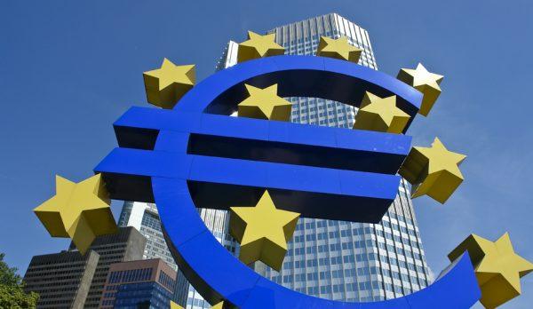Символ евро на фоне небоскрёбов