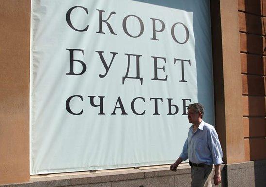 Человек и плакат «Скоро будет счастье»