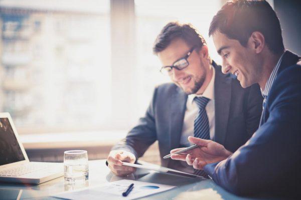 Мужчины за столом с бумагами и ноутбуком
