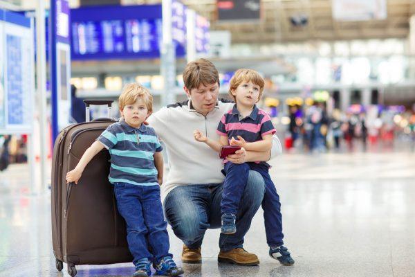 Мужчина с детьми и чемоданом в аэропорту