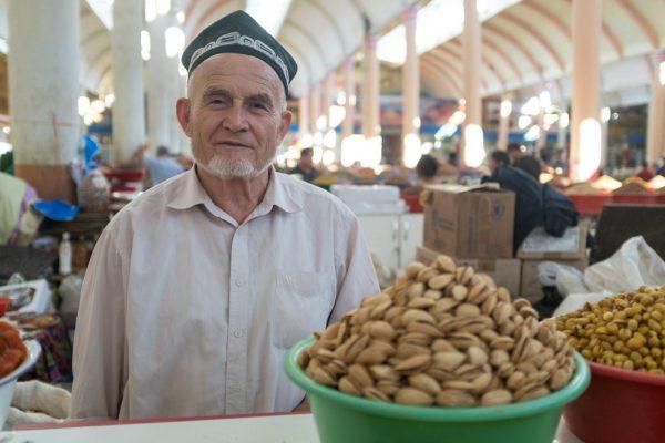 Продавец орехов на базаре в Таджикистане