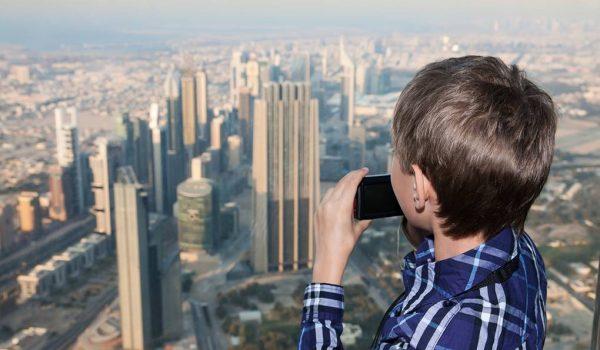 Мальчик с фотоаппаратом на фоне Дубая