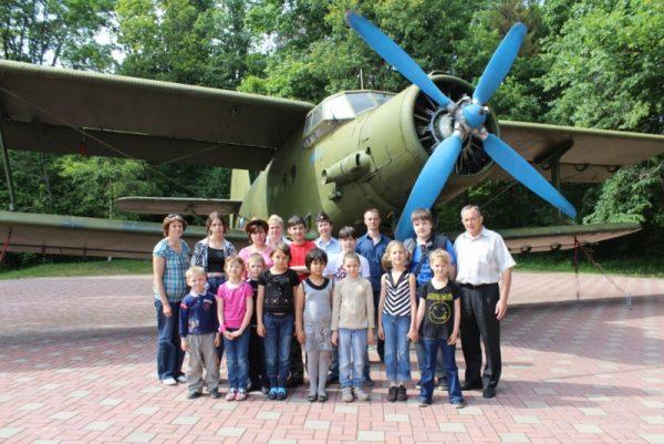 Группа школьников с взрослыми возле боевого самолёта на Партизанской поляне