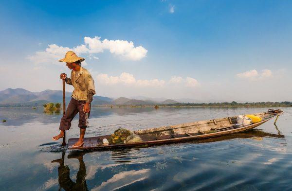 Местный житель плывёт на лодке по озеру Инле