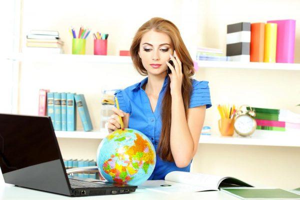 Девушка с глобусом и ноутбуком разговаривает по телефону
