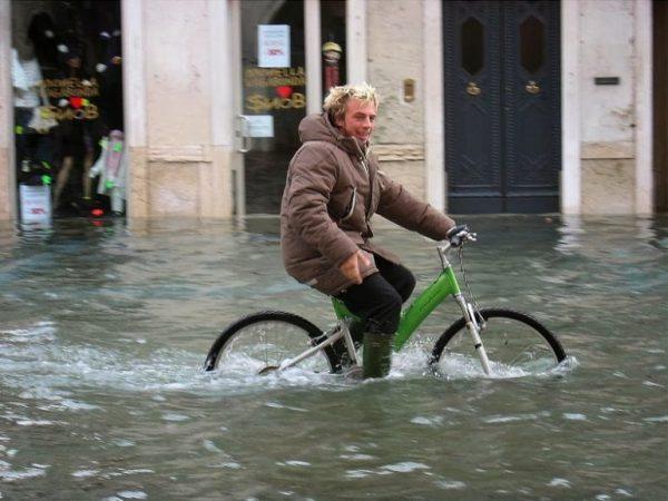 Мужчина передвигается по Венеции на велосипеде во время наводнения