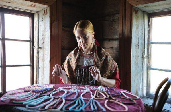 На столе лежат украшения из бисера, мастерица держит в руках нить
