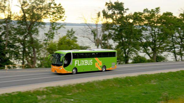 Автобус компании Flixbus едет по дороге вдоль моря