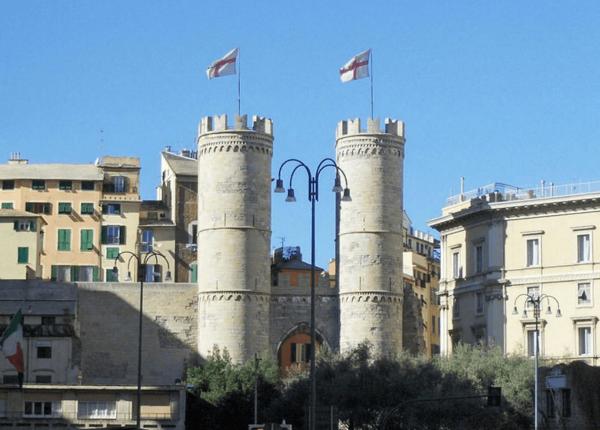 Башни ворот Порта Сопрана на фоне домов
