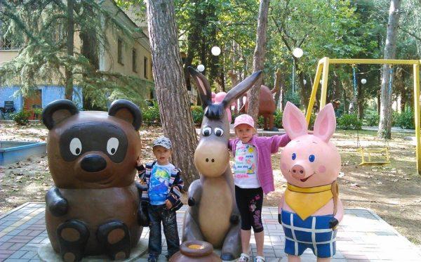 Дети рядом со скульптурами Винни-Пуха, Пятачка и ослика Иа