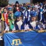 Дети в национальных костюмах держат флаг