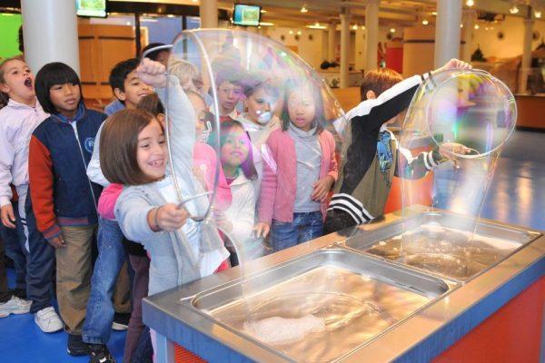 Девочка играет с большим мыльным пузырём