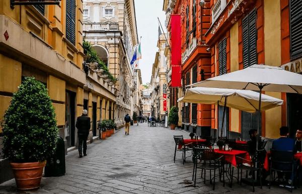 Здания домов и столики кафе на улице Гарибальди в Генуе