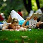 Люди читают книги, лёжа на траве в парке