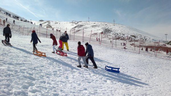 Люди с санками взбираются на холм Эльмадаг