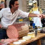 Мужчина-продавец предлагает попробовать кусочек колбасы
