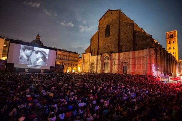 Зрители смотрят фильм в открытом кинотеатре