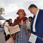 Девушка в национальном костюме показывает мужчине, как правильно прясть и ткать