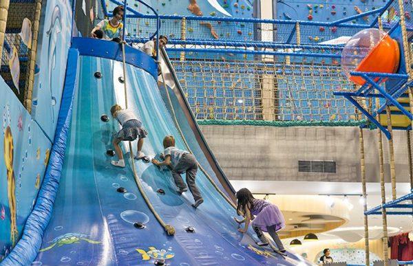 Дети взбираются по надувной горке в развлекательном парке