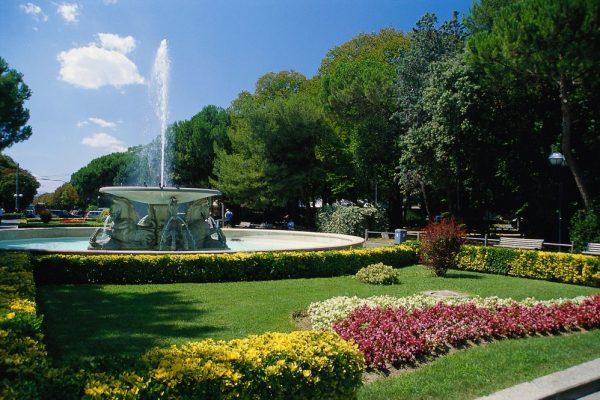 Фонтан и цветочные клумбы в парке Феллини