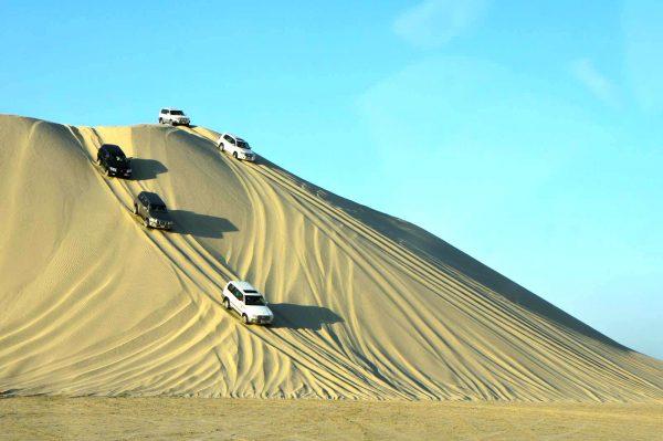 Машины спускаются с песчаной дюны