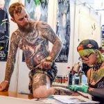Мастер делает татуировку мужчине