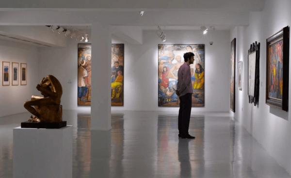 Мужчина рассматривает картину в музее