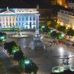 Фонтаны и здания на площади Россиу при вечернем освещении