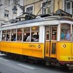 Люди едут в старинном лиссабонском трамвае
